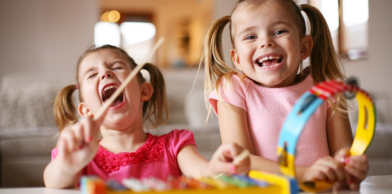 two little kids on a kids xylophone having great fun