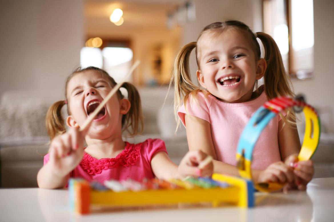 two little kids on a kids xylophone having great fun