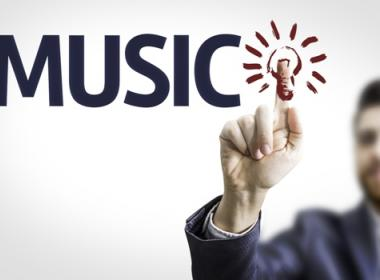 Man putting his finger on a light bulb image next to the word music