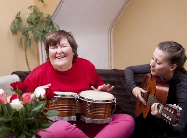 Young student playing music with her teacher