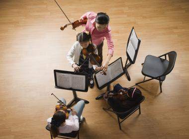 Aerial view of three music stands, two students and a teacher